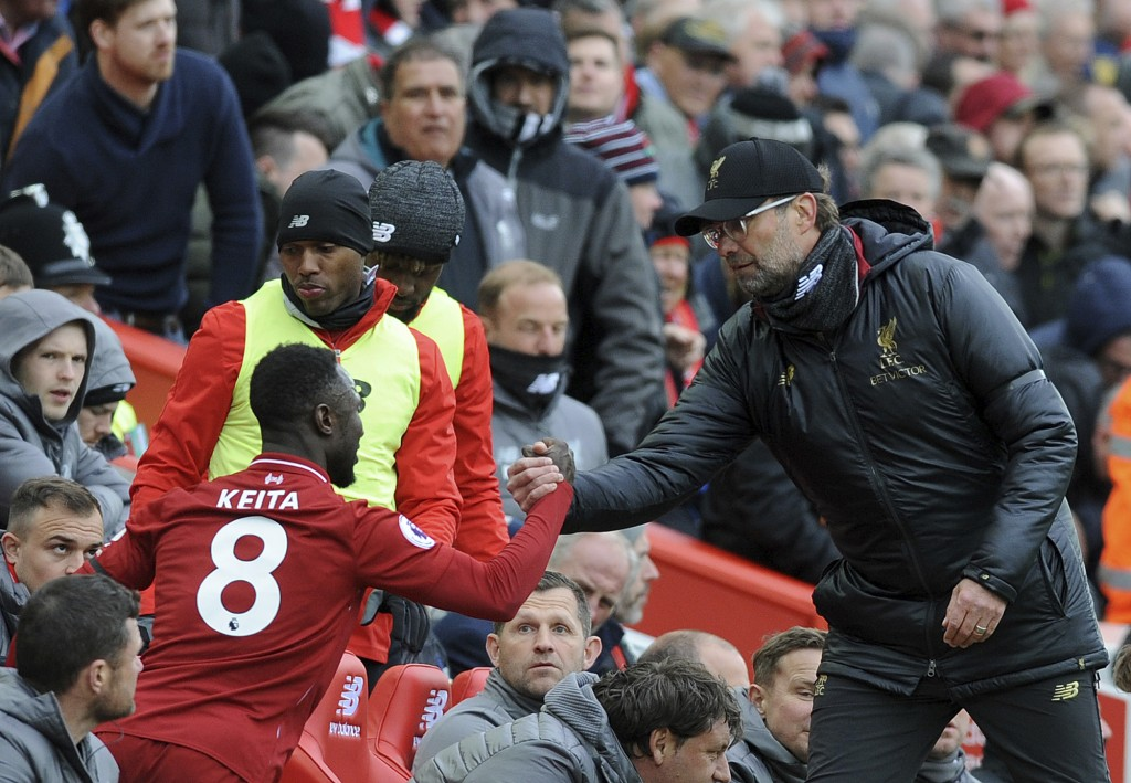 Liverpool manager Juergen Klopp, right, shakes hands with Liverpool's Naby Keita during the English Premier League soccer match between Liverpool and