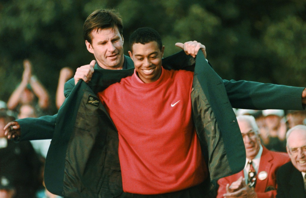 FILE - In this April 13, 1997, file photo, Masters champion Tiger Woods receives his Green Jacket from last year's winner Nick Faldo, rear, at the Aug