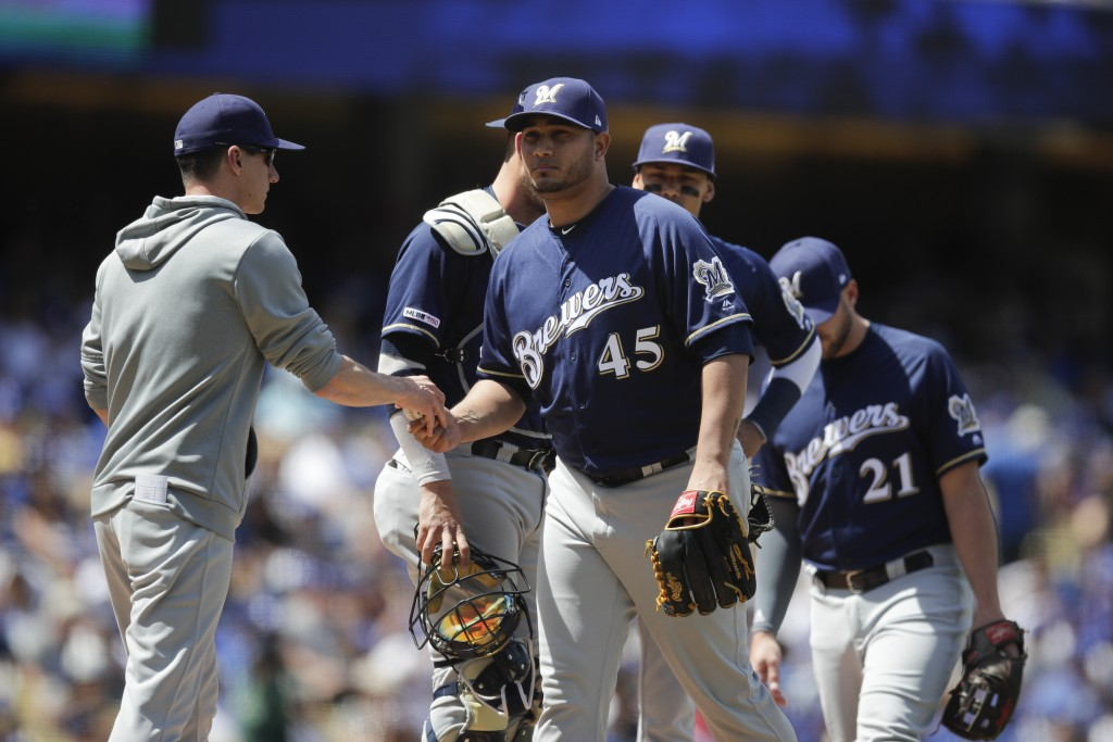 Milwaukee Brewers starting pitcher Jhoulys Chacin, center, is relieved by manager Craig Counsell during the third inning of a baseball game against th