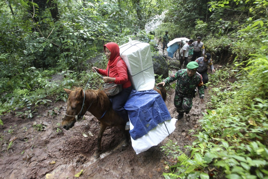 In this Monday, April 15, 2019, file photo, police officers and soldiers escort electoral workers using horses to distribute ballot boxes and other el