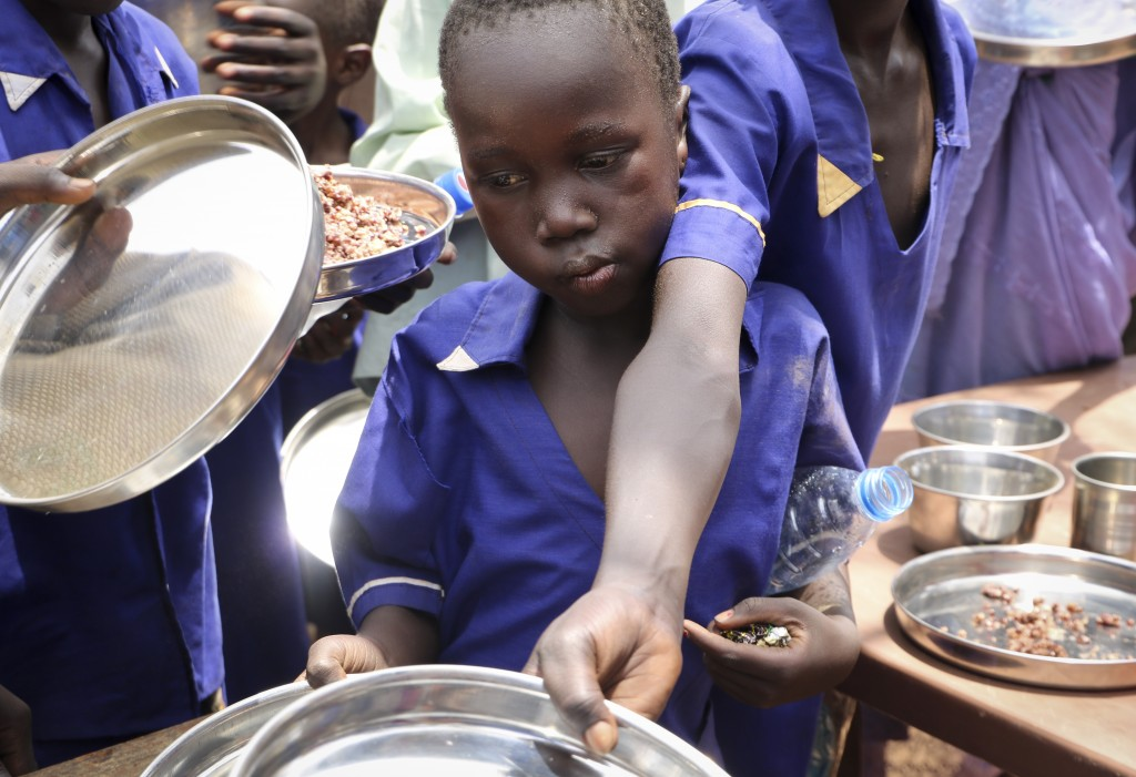 In this photo taken Tuesday, March 26, 2019, children push their plates out to receive a portion of cooked grains during a lunchtime feeding program i