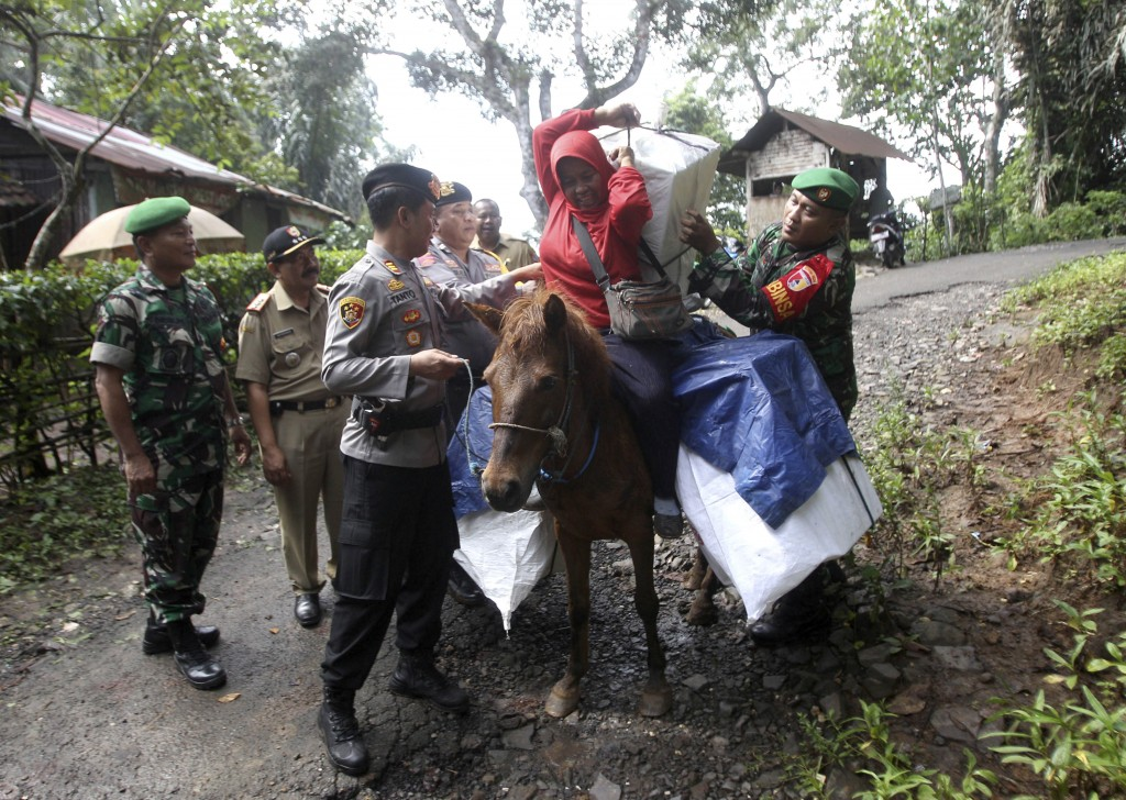 Police officers and soldiers assist a worker to carry ballot boxes and other election paraphernalia as they use horses to distribute them to polling s