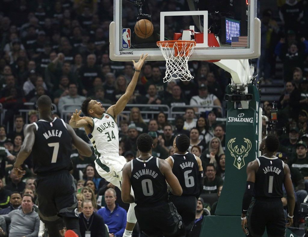 Milwaukee Bucks' Giannis Antetokounmpo (34) shoots against multiple Detroit Pistons defenders during the first half of Game 1 of an NBA basketball fir