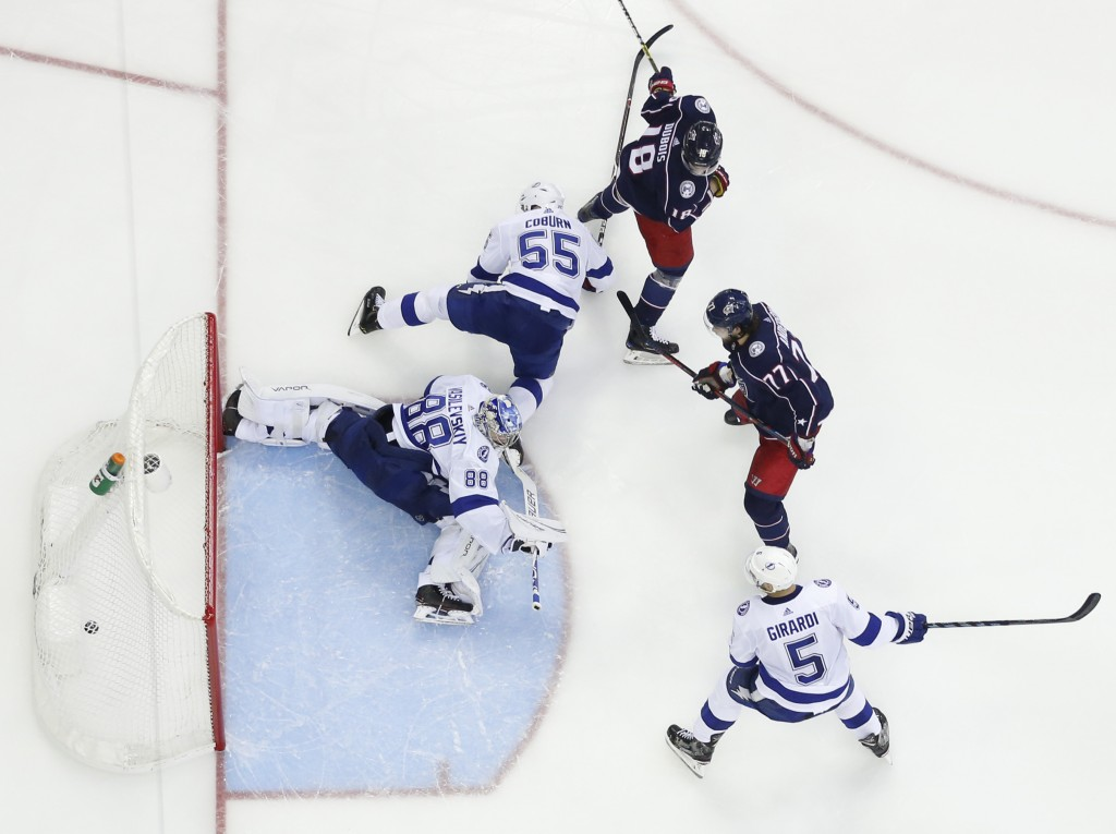 Tampa Bay Lightning's Andrei Vasilevskiy, left, of Russia, gives up a goal as Columbus Blue Jackets' Pierre-Luc Dubois, center, and Josh Anderson watc