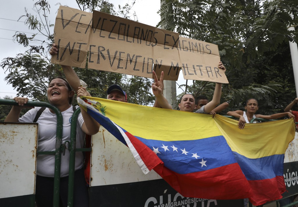 "People hold a Venezuelan flag and the Spanish message: ""Venezuelans demand military intervention,"" on the sidelines of a visit by U.S. Secretary of St..."