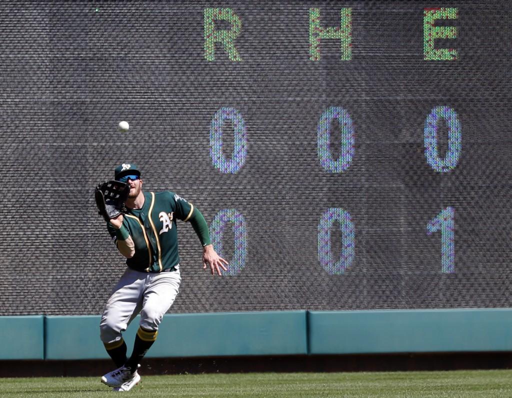 Oakland Athletics left fielder Robbie Grossman positions himself under a Texas Rangers' Asdrubal Cabrera fly-out in the fourth inning of a baseball ga...