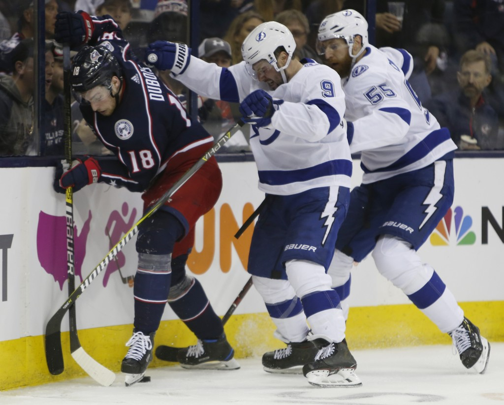 Columbus Blue Jackets' Pierre-Luc Dubois, left, keeps the puck away from Tampa Bay Lightning's Tyler Johnson, center, and Braydon Coburn during the se