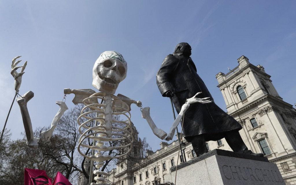 A skeleton is carried past the Winston Churchill statue as demonstrators take part in a 'Funeral Procession' during a climate protest in Parliament Sq