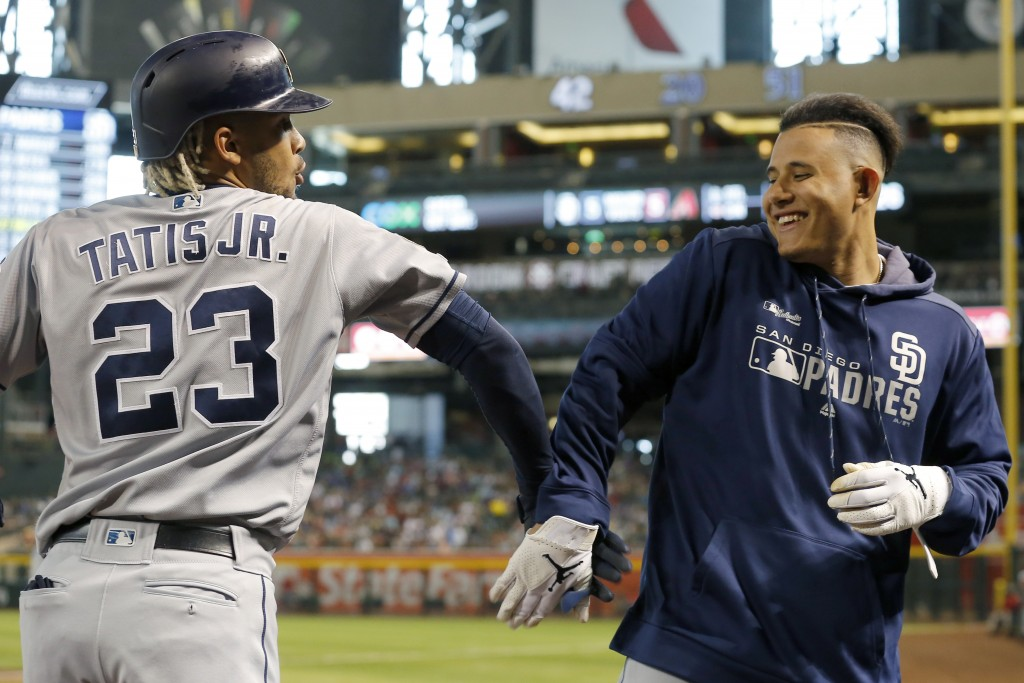 San Diego Padres Fernando Tatis Jr. (23) celebrates with Manny Machado after hitting a solo home run against the Arizona Diamondbacks in the fifth inn
