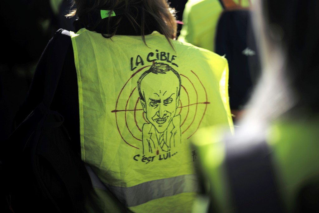"FILE - In this Feb.23, 2019 file photo, a protester wears a a yellow vest with a drawing depicting French President Emmanuel Macron and the word ""targ"