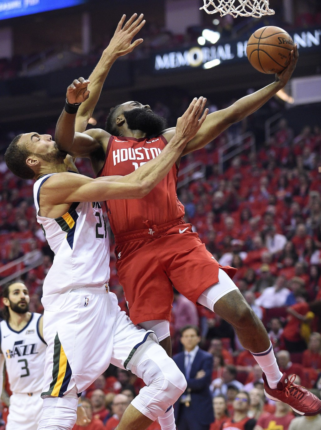 Houston Rockets guard James Harden, right, drives to the basket as Utah Jazz center Rudy Gobert defends during the first half of Game 1 of an NBA bask