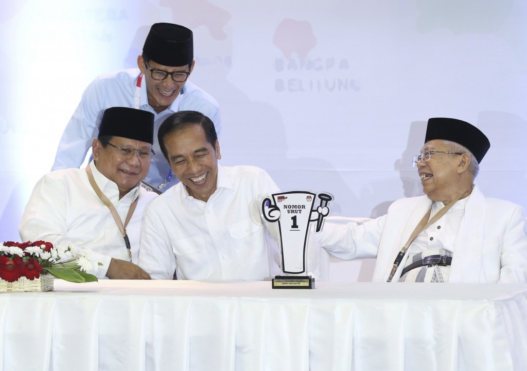 In this Sept. 21, 2018, photo, Indonesian presidential candidates, Prabowo Subianto, seated left, and Joko Widodo, second from left, share a light mom