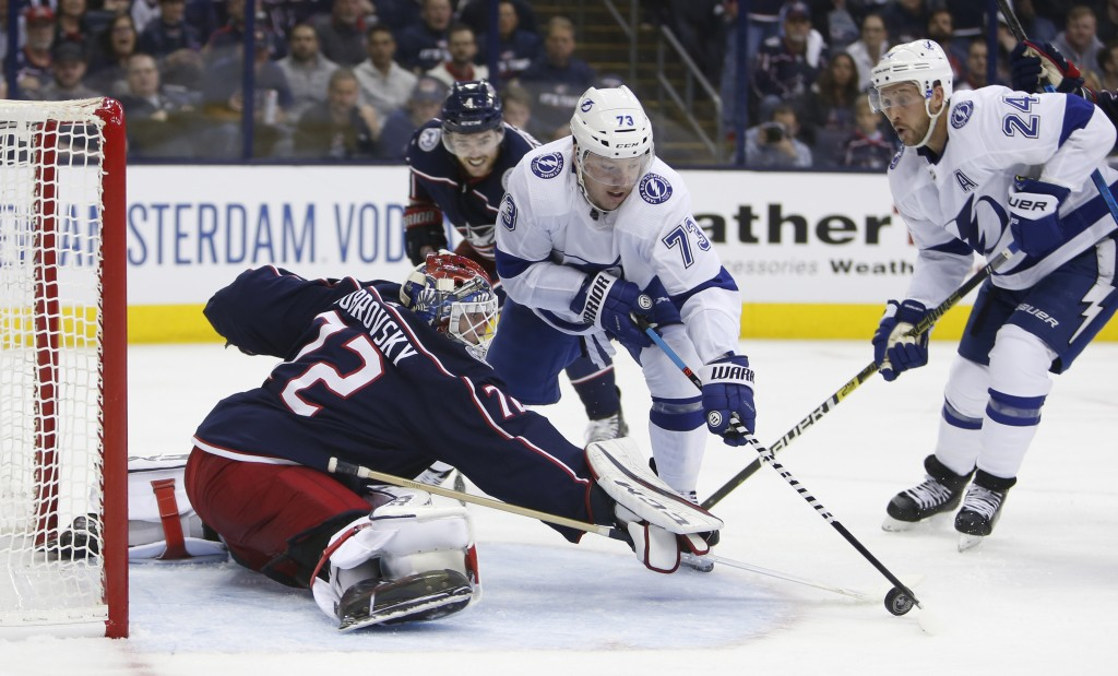 Columbus Blue Jackets' Sergei Bobrovsky, left, of Russia, makes a save against Tampa Bay Lightning's Adam Erne during the third period of Game 3 of an