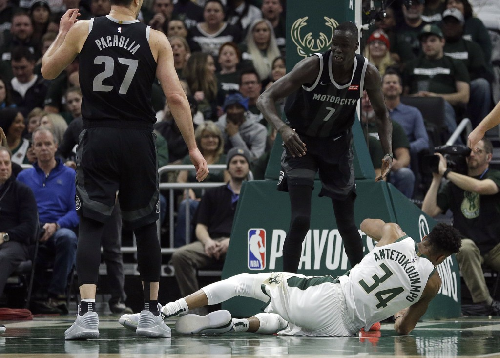 Milwaukee Bucks' Giannis Antetokounmpo (34) falls to the floor after being fouled by Detroit Pistons' Thon Maker (7) during the first half of Game 1 o