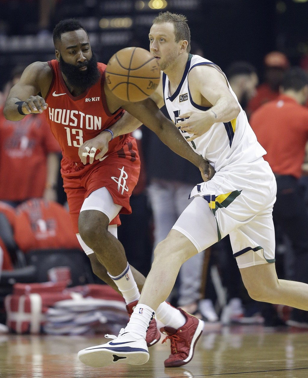 Utah Jazz forward Joe Ingles, right, passes the ball as Houston Rockets guard James Harden defends during the first half of Game 1 of an NBA basketbal