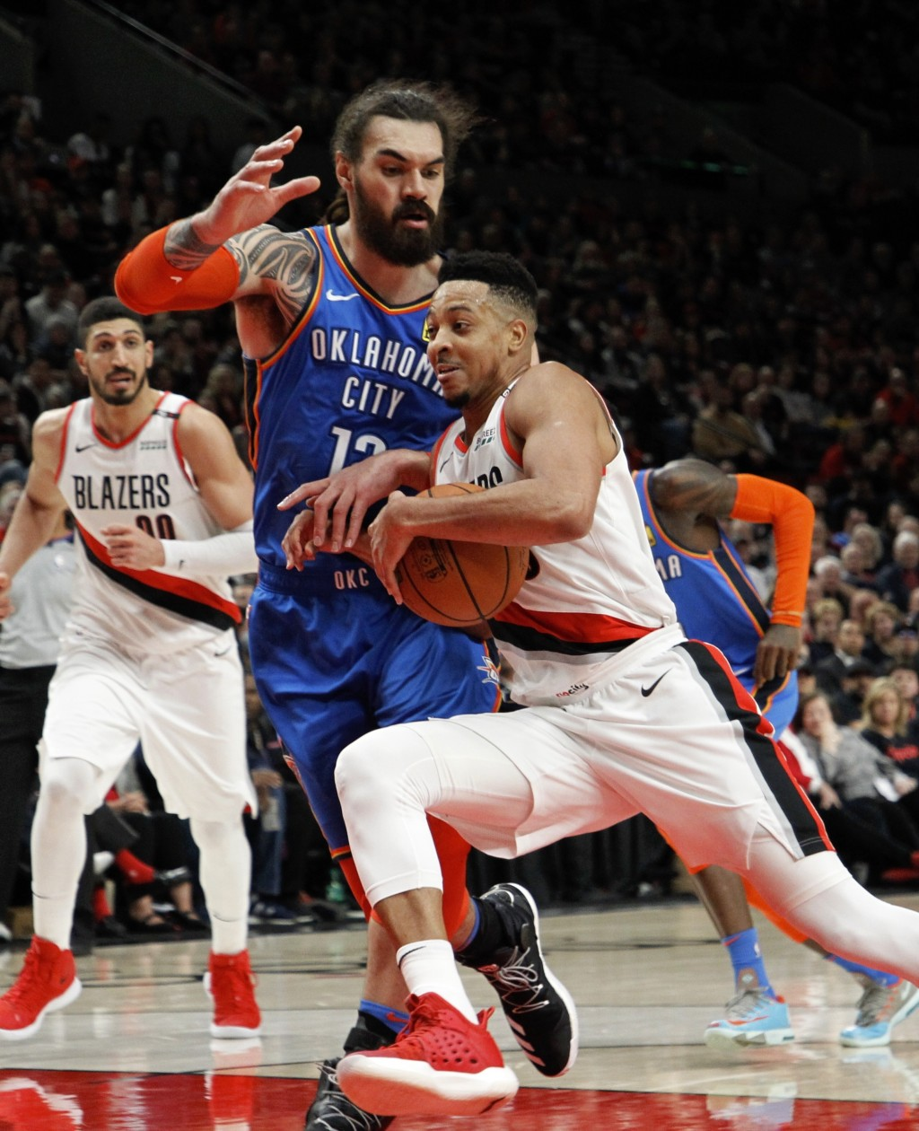 Portland Trail Blazers guard CJ McCollum, right, drives against Oklahoma City Thunder center Steven Adams, front left, during the second half of Game