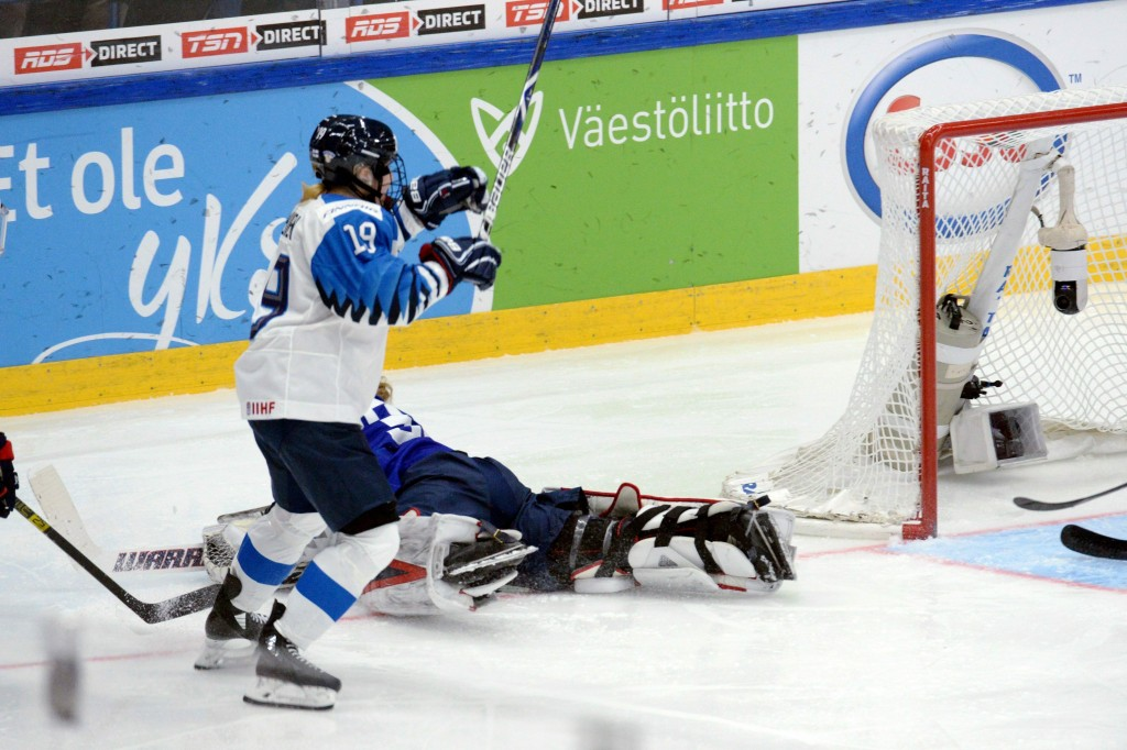 CORRECTS NAME OF FINNISH PLAYER TO PETRA NIEMINEN- Goalkeeper Alex Rigsby of the United States lies on the ice while Petra Nieminen of Finland starts