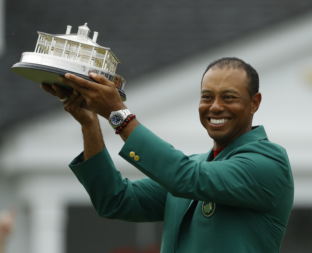 Tiger Woods wears his green jacket holding the winning trophy after the final round for the Masters golf tournament Sunday, April 14, 2019, in Augusta