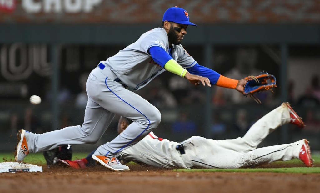 Atlanta Braves' Ozzie Albies steals second base as New York Mets shortstop Amed Rosario misses a wild throw by catcher Wilson Ramos during the third i