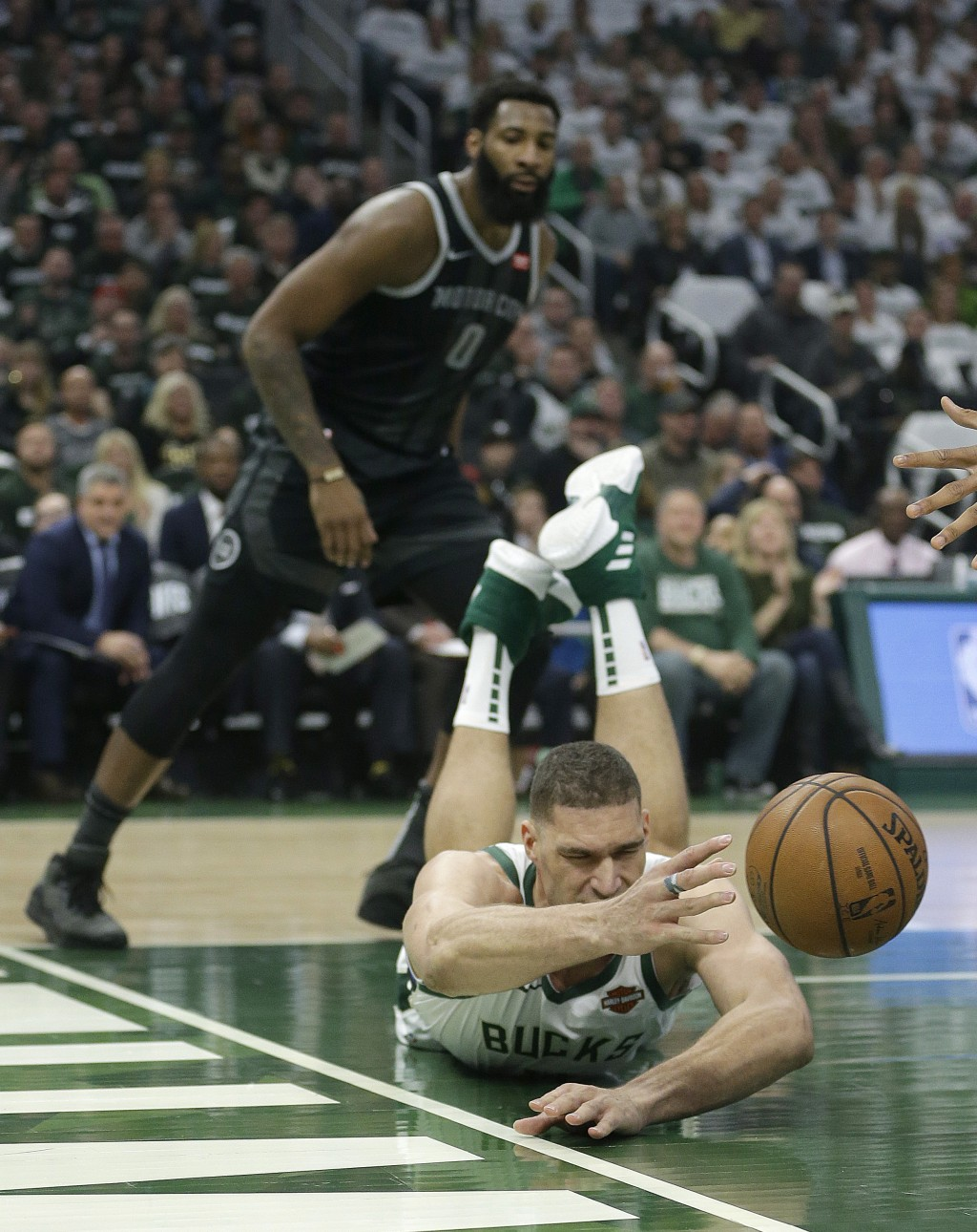 Milwaukee Bucks' Brook Lopez is unable to save the ball from going out of bounds in front of Detroit Pistons' Andre Drummond during the first half of