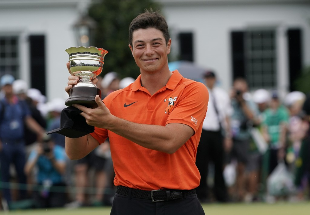 Viktor Hovland, of Norway, holds up his low amateur trophy after the Masters golf tournament, Sunday, April 14, 2019, in Augusta, Ga. (AP Photo/David