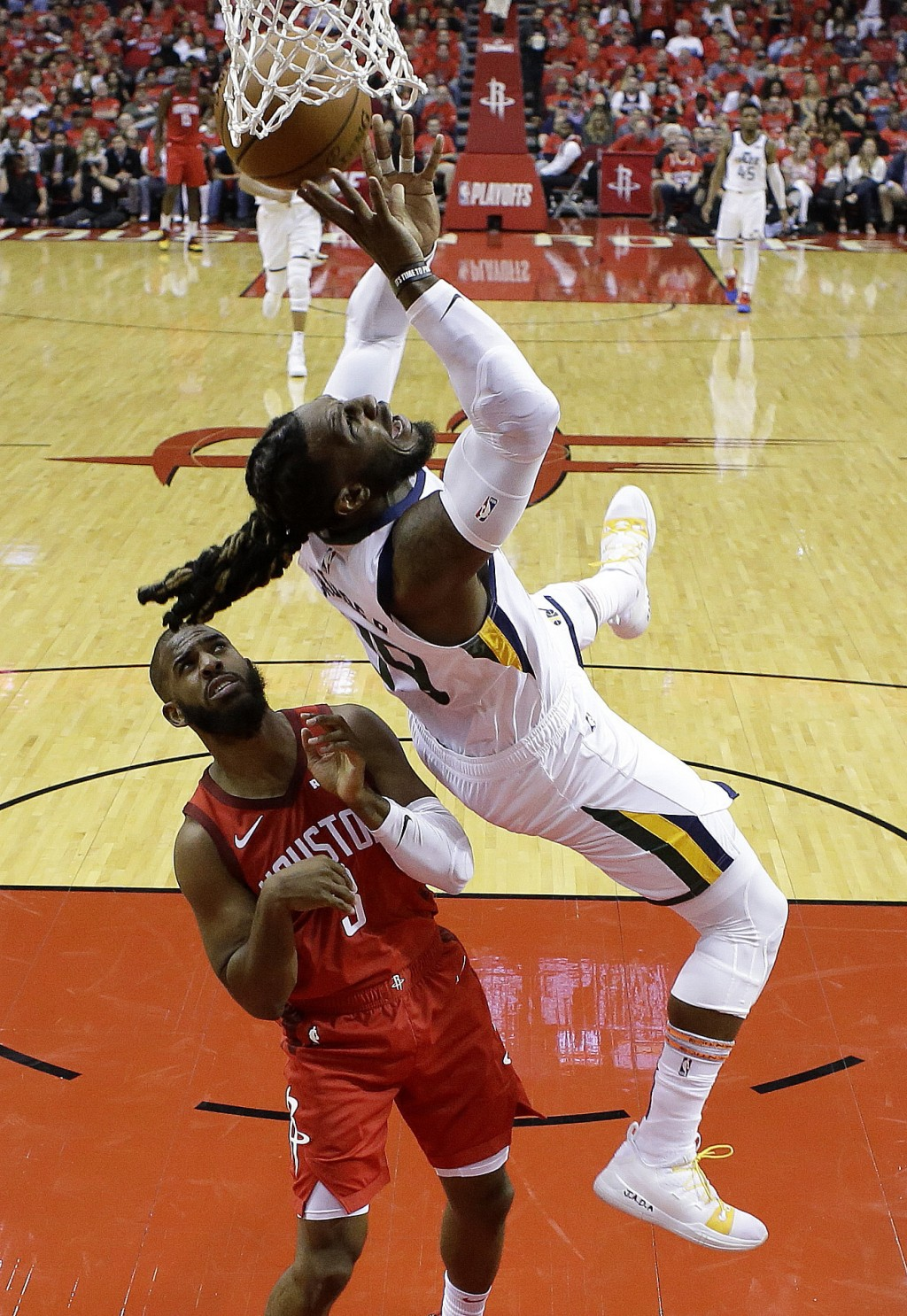 Utah Jazz forward Jae Crowder, right, falls over Houston Rockets guard Chris Paul while driving to the basket during the first half of Game 1 of an NB