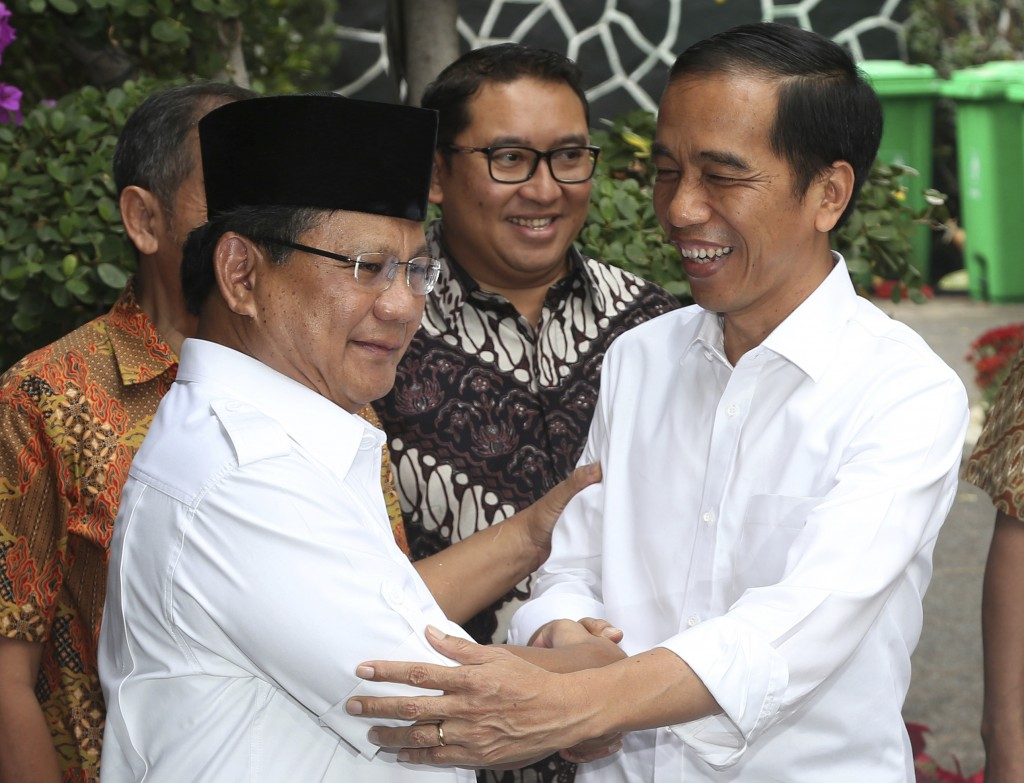 FILE - In this Oct. 17, 2014, file photo, then Indonesia's President-elect Joko Widodo, right, greets his political rival Prabowo Subianto during a me