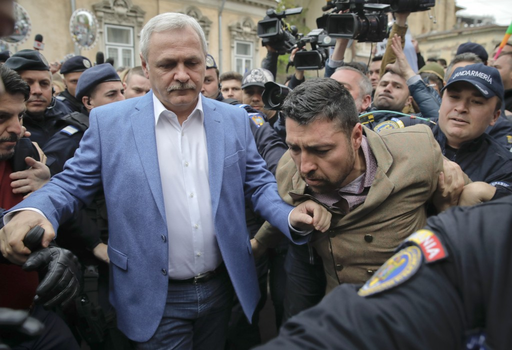 Liviu Dragnea, left, the leader of Romania's ruling Social Democratic party, arrives escorted by police officers for court hearing in a trial in Bucha