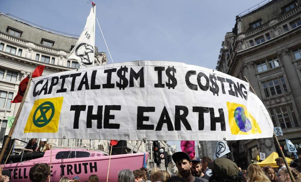 Protesters take part holding placards during a climate change demonstration in London, Monday, April 15, 2019. Extinction Rebellion have organised a n