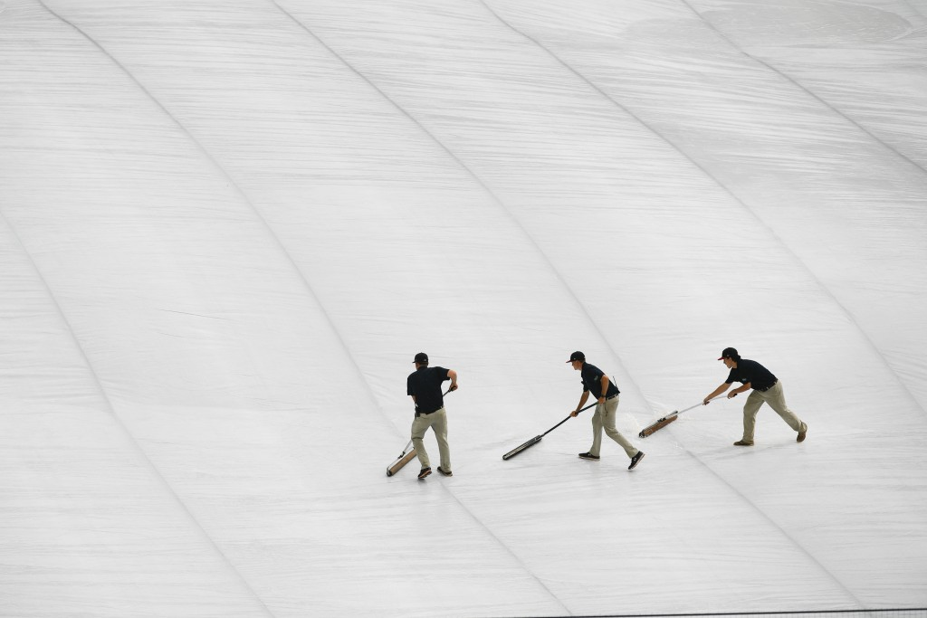 Atlanta Braves grounds crew roll water off a tarp covering the infield before a delay in the start of a baseball game against the New York Mets was an