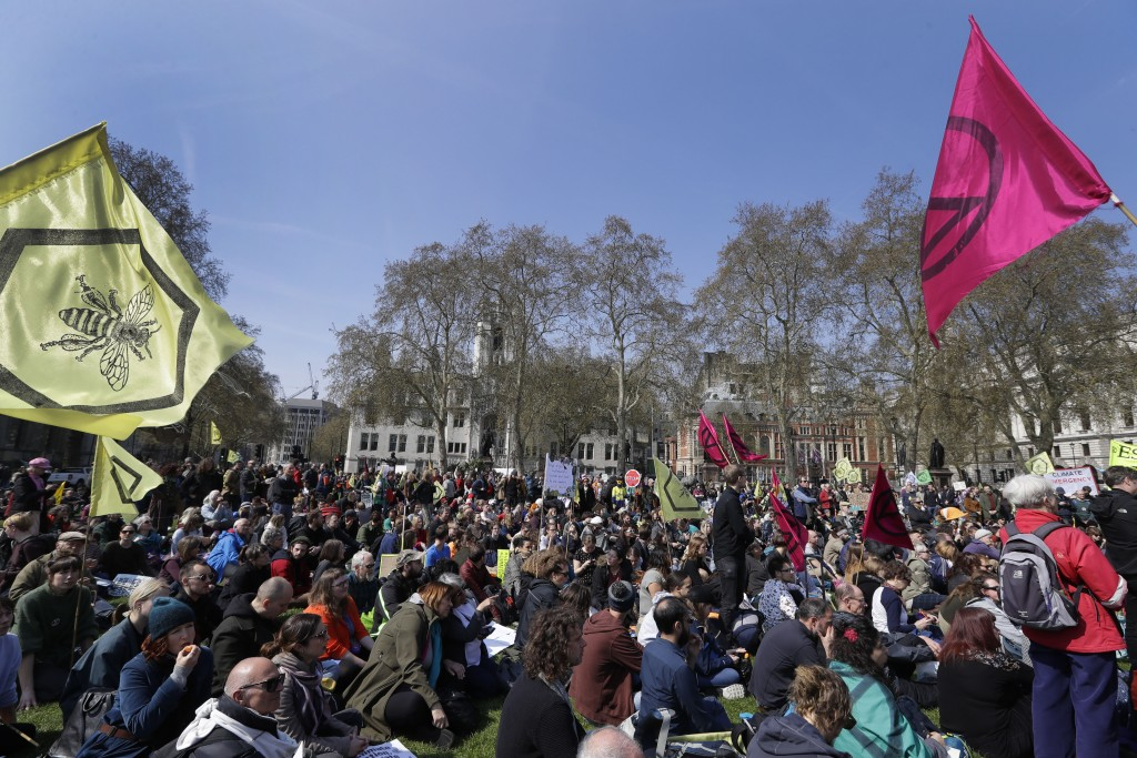 Demonstrators listen to speakers during a climate protest in Parliament Square in London, Monday, April 15, 2019. Extinction Rebellion have organised ...