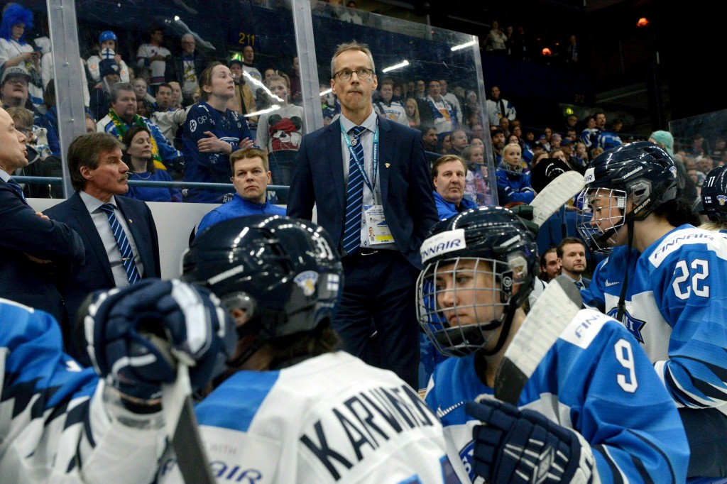 Finnish head coach Pasi Mustonen and players look dejected after their 2-1 shootout loss in the IIHF Women's Ice Hockey World Championships final matc