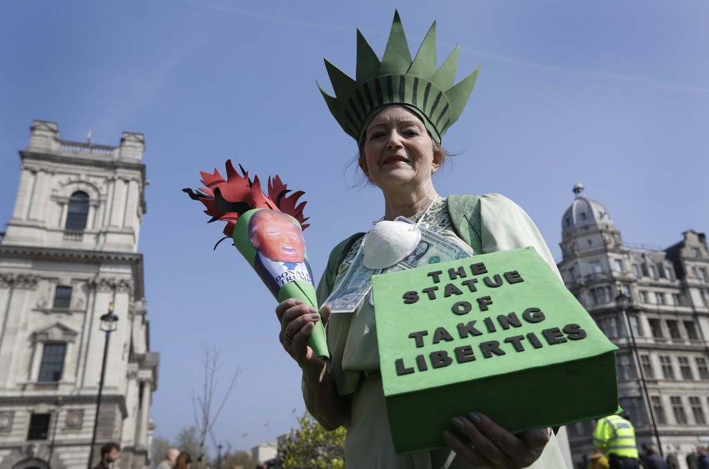 A demonstrator holds a banner during a climate protest in Parliament Square in London, Monday, April 15, 2019. Extinction Rebellion have organised a n