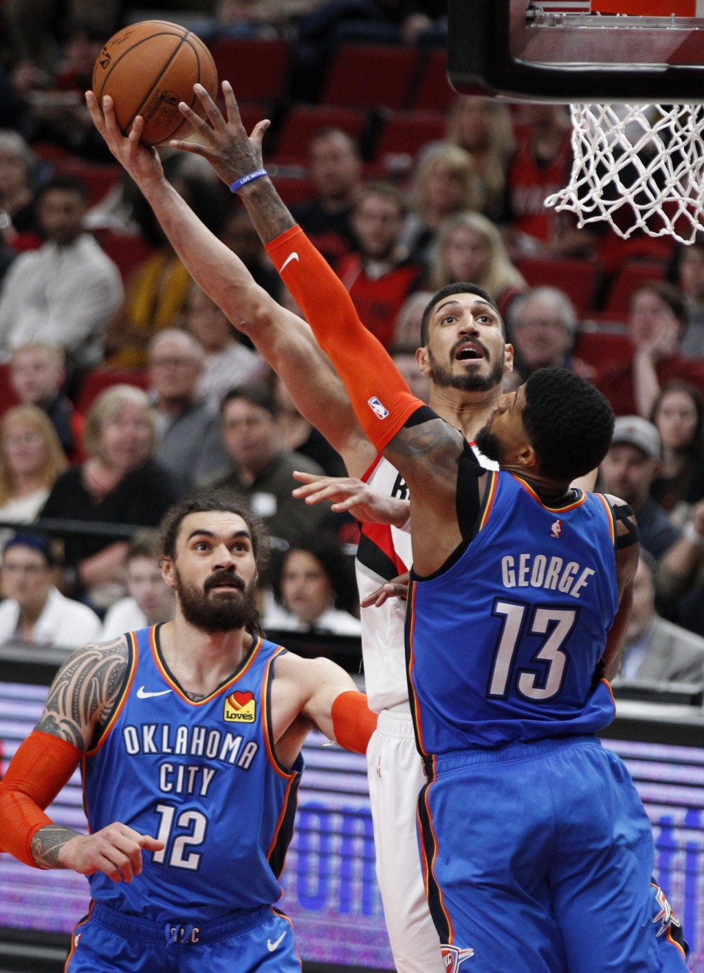 Portland Trail Blazers center Enes Kanter, center, shoots as Oklahoma City Thunder center Steven Adams, left, and forward Paul George, right, defend d