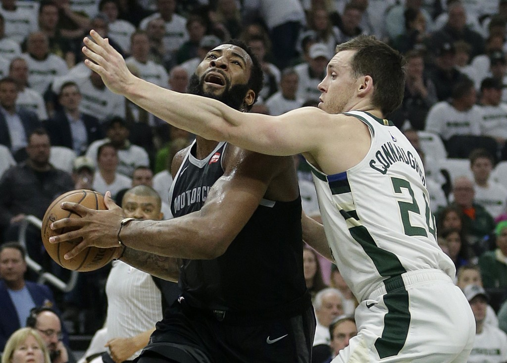 Detroit Pistons' Andre Drummond, left, drives to the basket against Milwaukee Bucks' Pat Connaughton during the first half of Game 1 of an NBA basketb