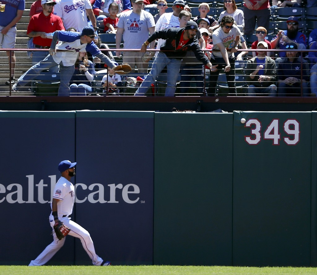 Texas Rangers right fielder Nomar Mazara watches a fans reach out for a Oakland Athletics' Khris Davis double in the first inning of a baseball game i