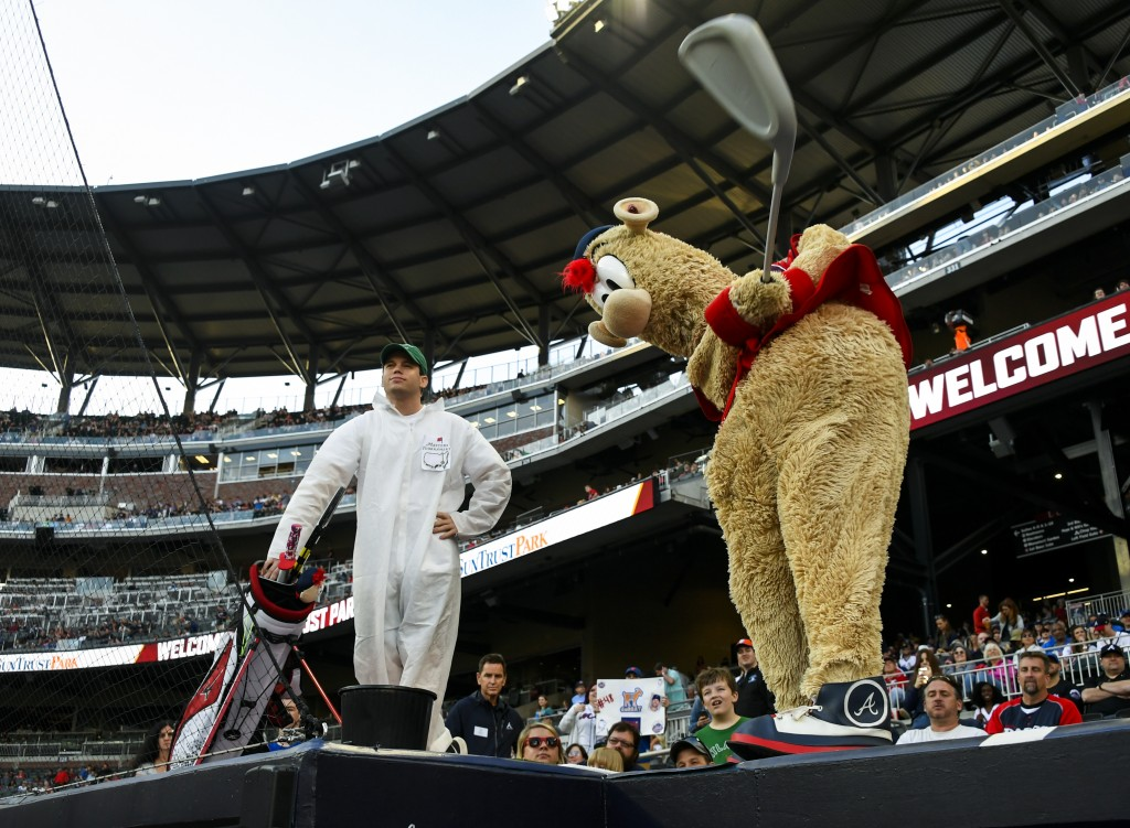 """Atlanta Braves mascot """"Blooper,"""" right, tees off from the top of a dugout as his Masters-clad caddie stands by before a baseball game against the New"""