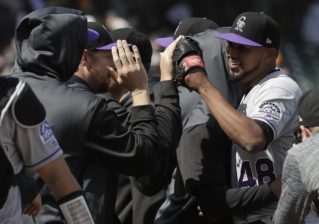 Colorado Rockies pitcher German Marquez, right, celebrates with teammates after they defeated the San Francisco Giants in a baseball game in San Franc
