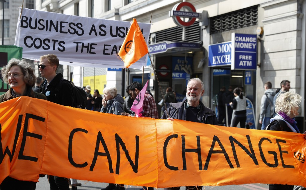 """Climate change protesters hold up a banner saying 'We can Change"""" during a demonstration in London, Monday, April 15, 2019. Extinction Rebellion have"""