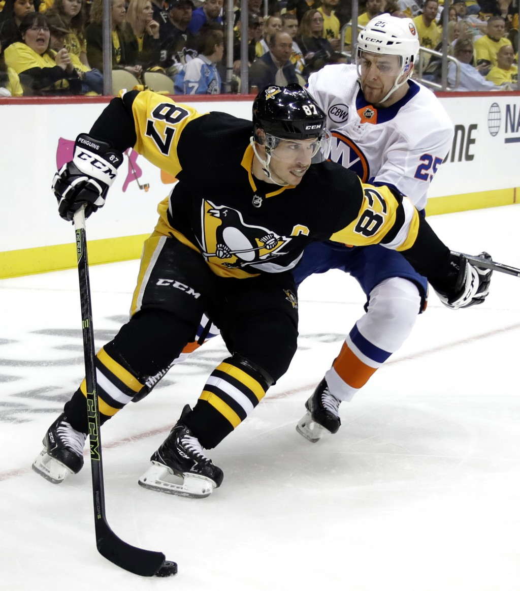 Pittsburgh Penguins' Sidney Crosby (87) holds off New York Islanders' Devon Toews (25) during a second period power play in Game 3 of an NHL first-rou