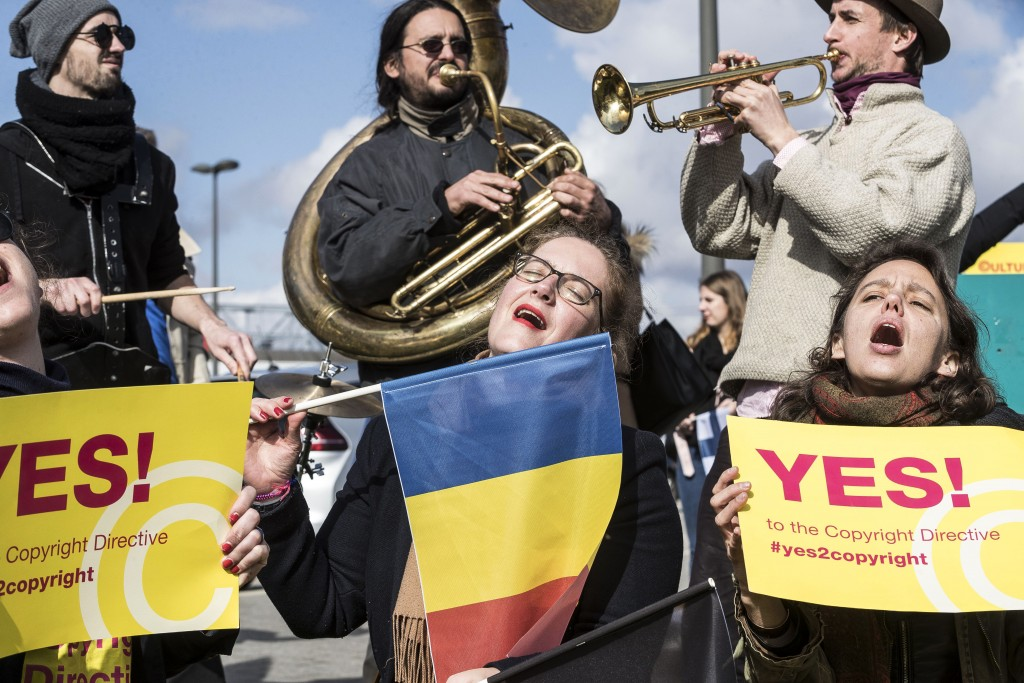 FILE - In this Tuesday March 26, 2019 file photo, people gather at the front of the European Parliament building in Strasbourg, France, to show their ...