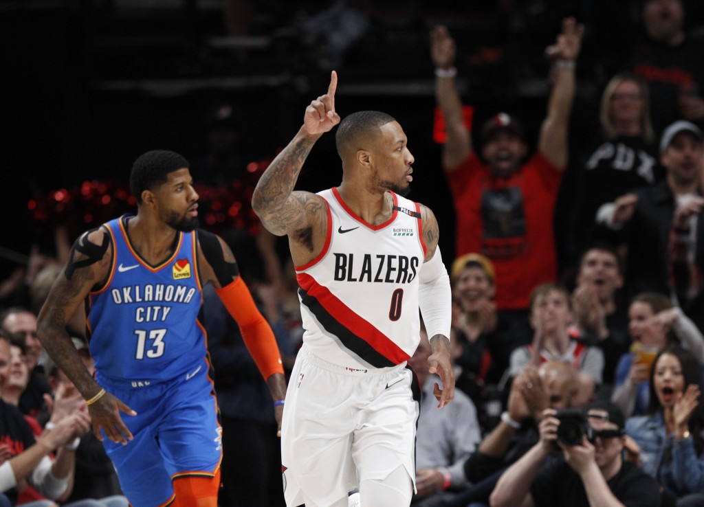 Portland Trail Blazers guard Damian Lillard, right, reacts after making a basket as Oklahoma City Thunder forward Paul George, left, trails the play d