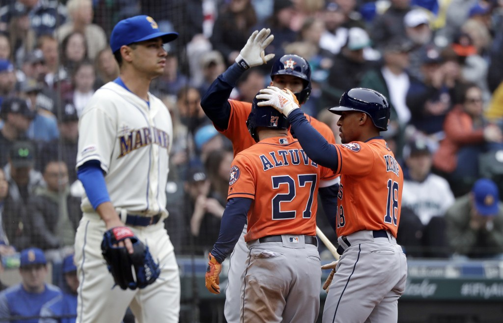 Seattle Mariners starting pitcher Marco Gonzales, left, heads back to the mound as Houston Astros' Jose Altuve (27) and Tony Kemp (18) celebrate scori