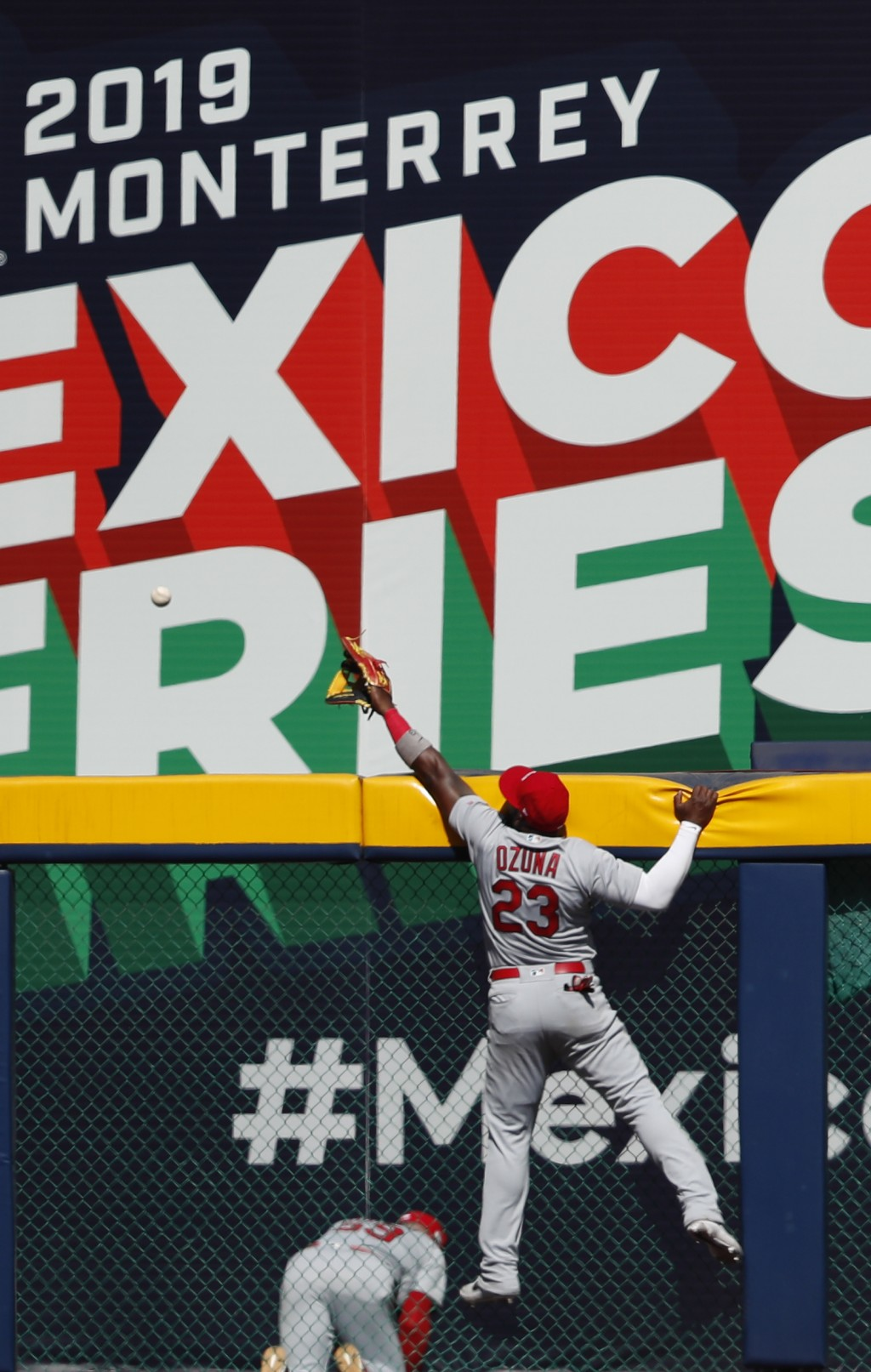 St. Louis Cardinals' Marcell Ozuna leaps but can't stop a 3-run home run by Cincinnati Reds' Jesse Winker during the fifth inning of a baseball game i