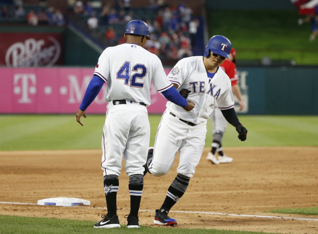 Texas Rangers third base coach Tony Beasley, left, congratulates Shin-Soo Choo, right, who hit a solo home run against the Los Angeles Angels during t...