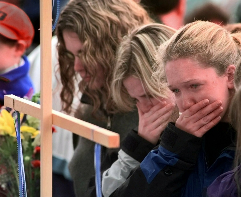 FILE - In this April 22, 1999, file photo, Columbine High School students, from left, Darcy Craig, Molly Byrne and Emily Dubin stop to pay their respe