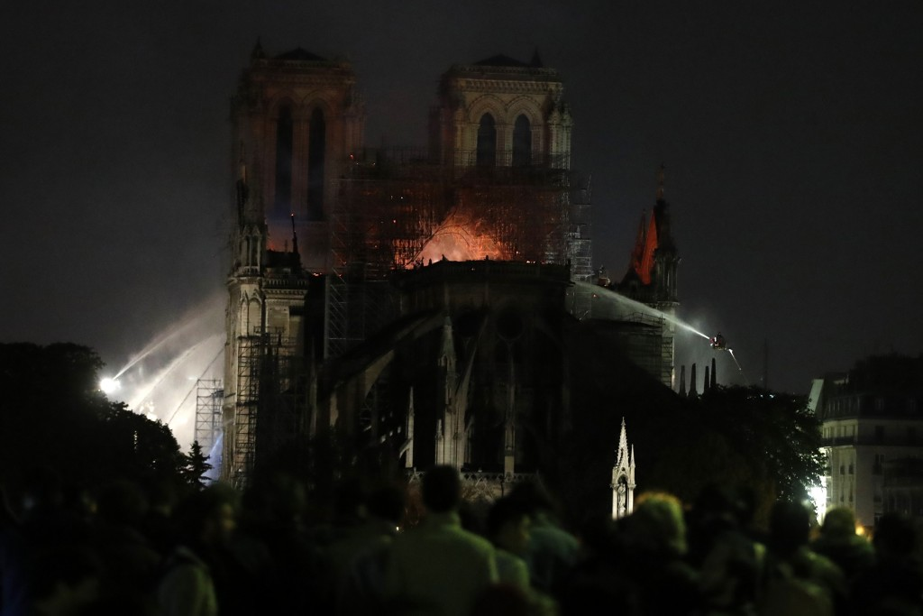 People watch Notre Dame cathedral burning in Paris, Monday, April 15, 2019. A catastrophic fire engulfed the upper reaches of Paris' soaring Notre Dam
