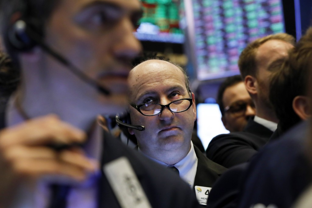 FILE - In this April 12, 2019, file photo trader Andrew Silverman, center, works on the floor of the New York Stock Exchange. The U.S. stock market op...