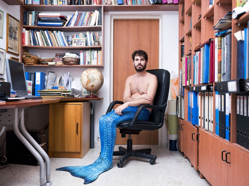 In this Wednesday, Feb. 20, 2019 photo, Yuval Avrami, a member of the Israeli Mermaid Community, poses for a portrait as he wears a tail at his home i