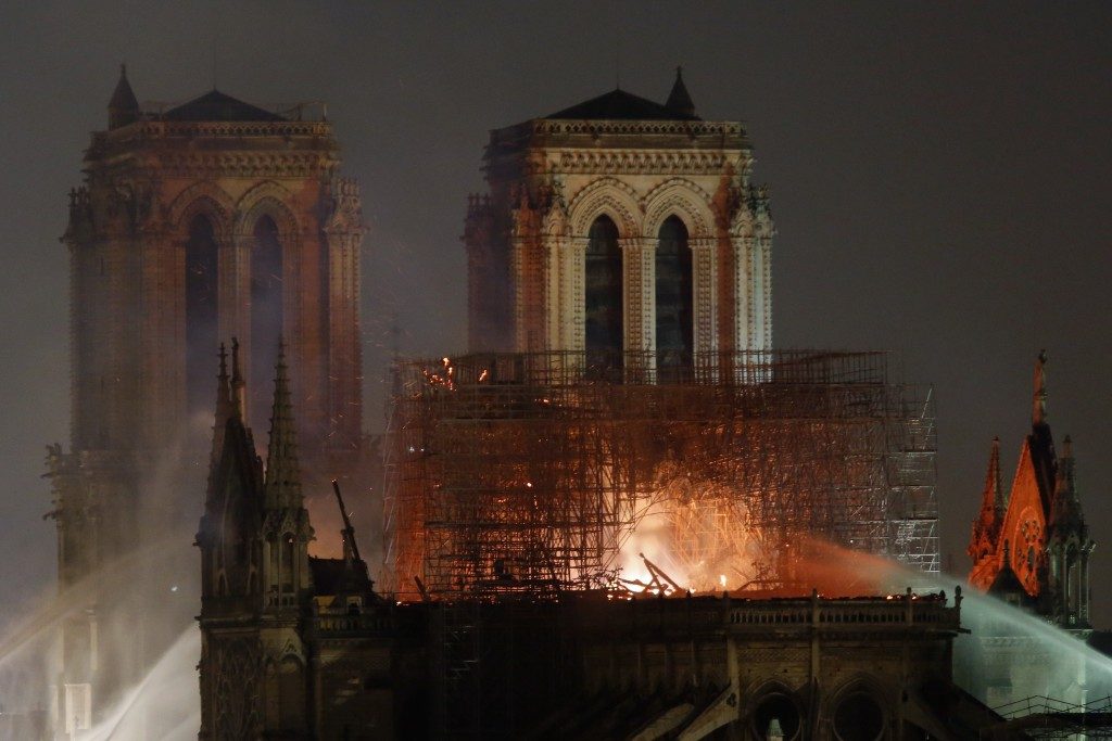 Firefighters tackle the blaze as flames and smoke rise from Notre Dame cathedral as it burns in Paris, Monday, April 15, 2019. Massive plumes of yello